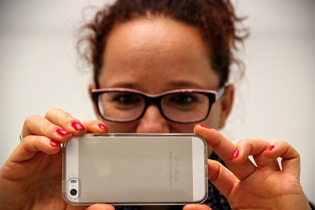 žena fotící iPhonem