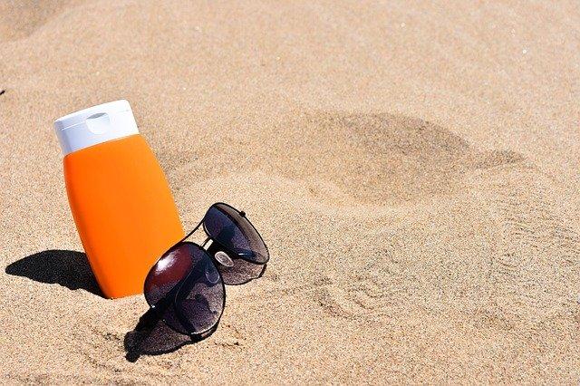 krém a brýle v písku