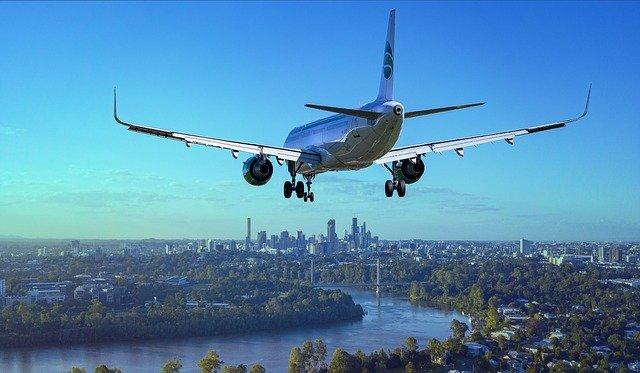 letadlo, které bude přistávat, je těsně nad místem přistání  městem