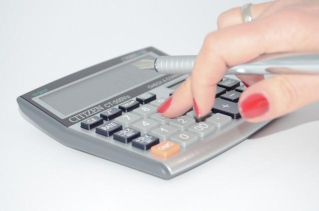 ruka počítající na kalkulačce